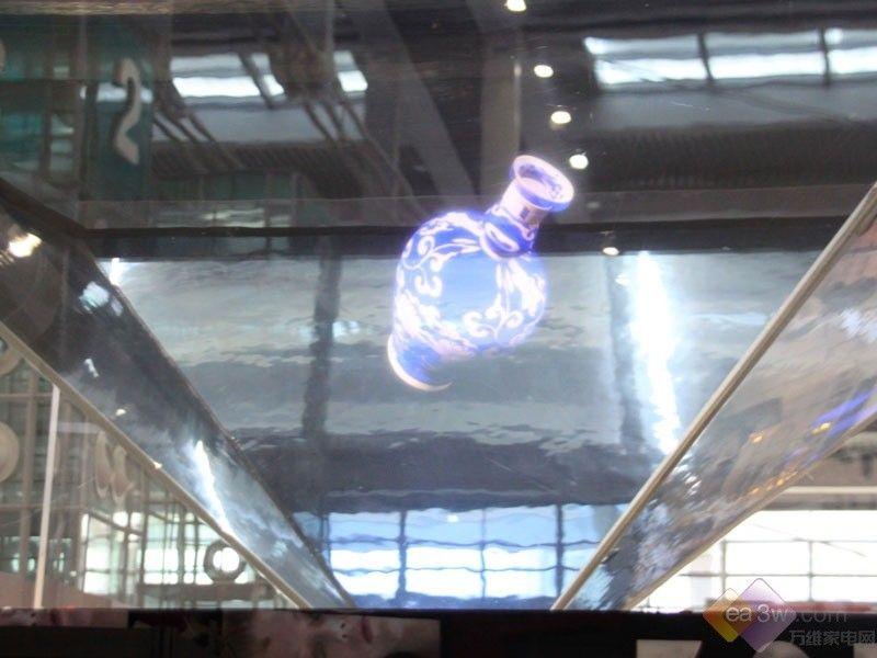 2011中国深圳消费电子展于4月8日~10日在深圳会展中心举行,各种独特的显示技术纷纷亮相。北京中视太和展示了最新的360度全息展示机柜,我们可以看到这款产品利用全息式、自由漂浮的绚丽图像来提供了亦幻亦真的视觉体验。   据悉这就是采用了360度全息投影技术,所谓360度幻影成像系统就是由透明材料制成的四面锥体,观众的视线能从任何一面穿透它,通过表面镜射和反射,观众能从锥形空间里看到自由飘浮的影像和图形。四个视频发射器将光信号发射到这个锥体中的特殊棱镜上,汇集到一起后形成具有真实维度空间的立体影像。